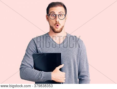 Young handsome caucasian man holding business folder scared and amazed with open mouth for surprise, disbelief face