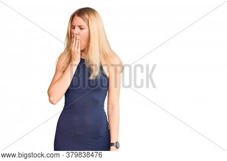 Young beautiful blonde woman wearing casual dress bored yawning tired covering mouth with hand. restless and sleepiness.