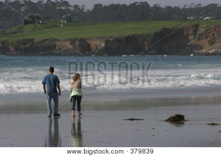 couple walking on the beach enjoying a beautiful day at pebble beach in california poster