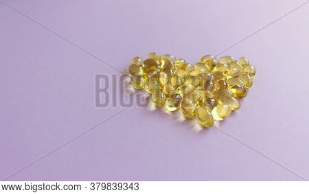 Yellow Gelatin Capsules In The Shape Of A Heart On A Lilac Background Close-up.