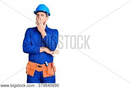 Young handsome man wearing worker uniform and hardhat bored yawning tired covering mouth with hand. restless and sleepiness.