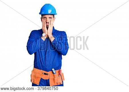 Young handsome man wearing worker uniform and hardhat worried and stressed about a problem with hand on forehead, nervous and anxious for crisis