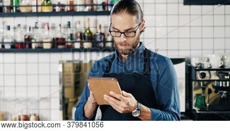 Male Caucasian Barmen In Glasses And Apron Using Tablet Device In Cafe At Kitchen. Handsome Young Ma