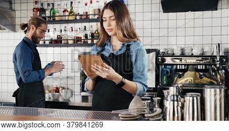 Pretty Caucasian Female Waitress In Apron Standing In Cafe At Counter, Using Tablet Device And Talki
