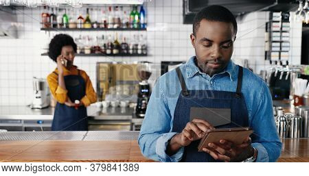 Portrait Of Male African American Barmen Using Tablet Device In Cafe And Smiling To Camera. Handsome