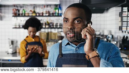 Close Up Of Male African American Barmen Talking On Mobile Phone In Cafe. Handsome Man Waiter Speaki