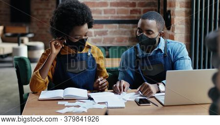 African American Couple In Masks Doing Business Calculations Of Restaurant And Checking Bills. Calcu