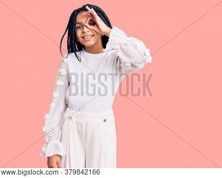 Cute african american girl wearing casual white tshirt doing ok gesture with hand smiling, eye looking through fingers with happy face.