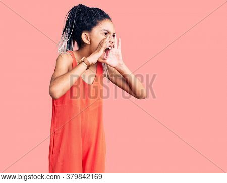 Cute african american girl wearing casual clothes shouting angry out loud with hands over mouth