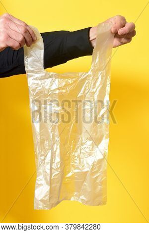 Man Holding A Plastic Bag On Yellow Background