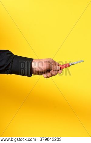 A Hand With Cutter On Yellow Background