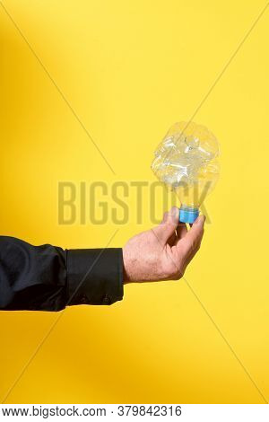 Man Holding A Crumpled Plastic Bottle On Yellow Background