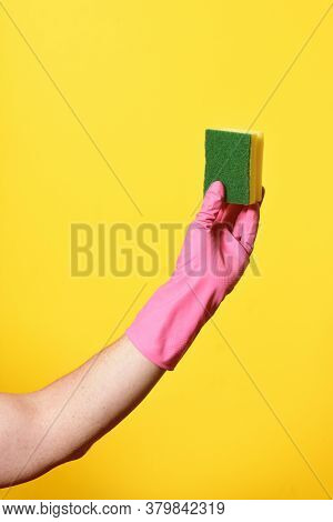 Hand With Glove Hoding Scourer On Yellow Background