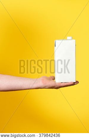 Man Holding A Container Carton On Yellow Background