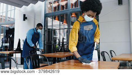 African American Couple Of Barristas, Male And Female In Masks Cleaning Desks In Cafeteria With Sani