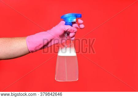Hand With Spray Bottle On Red Background