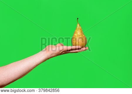 Hand Holding A Pear On Green Background