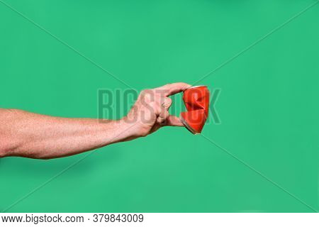 Hand Crushing A Tin Can On Green Background