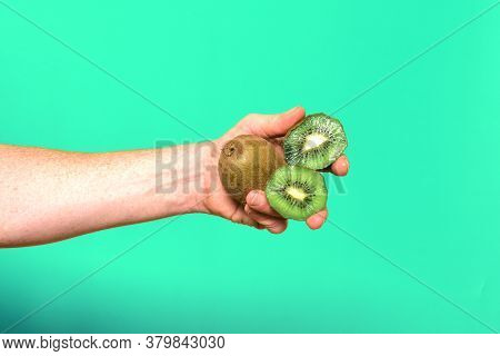 Hand Holding A Group Of Kiwis On Green Background