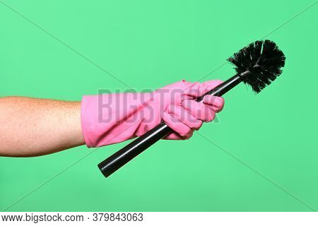 Hand With Glove Hoding Brush On Green Background