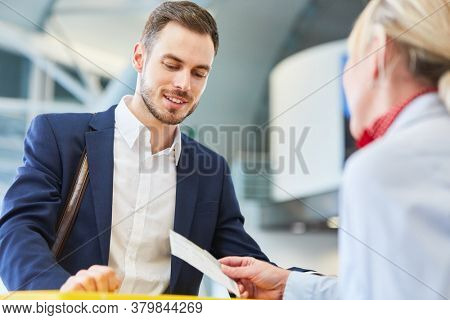 Service Agent checks boarding pass or plane ticket at the check-in desk in the airport
