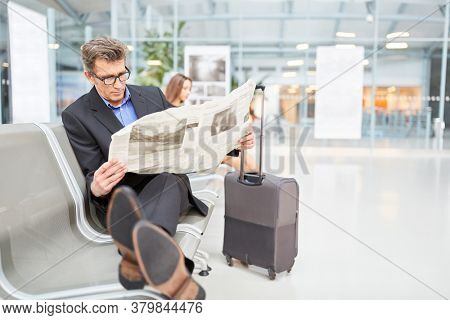 Businessman is waiting for his connecting flight and reading newspaper in the airport waiting area