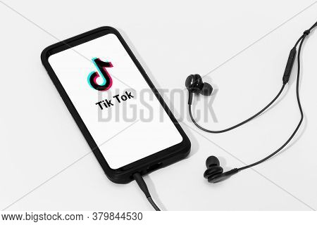Galicia, Spain; March 25, 2020 : Earphones And Smart Phone Screen With Tik Tok Logo