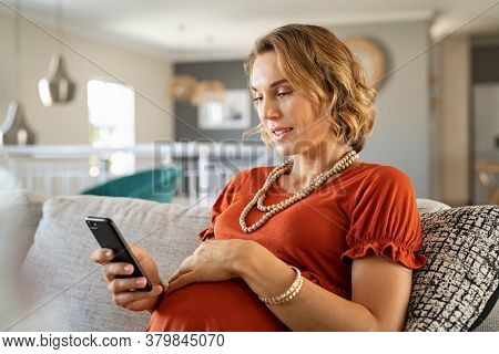 Pregnant middle aged woman sitting on couch and using phone. Mid adult expecting woman texting on mobile phone while relaxing on sofa at home. Pregnant lady using app on cellphone to monitor gestation