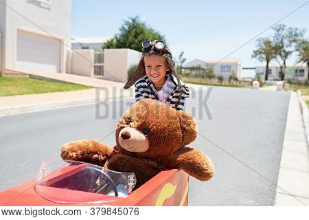 Little kid pushing big toy car and having fun playing with his teddy bear. Teddy bear enjoying pedal race car ride with little boy. Happy child playing with teddy bear and toy car on street.