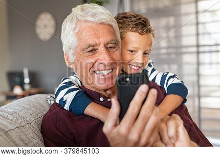Cute boy hugging old grandfather from behind while sitting on couch and using smartphone. Playful grandson embracing senior man while using phone. Elderly grandpa with child watching video on mobile.