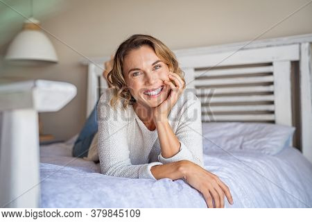 Young woman looking at camera and smiling while lying on bed at home. Pretty casual mid woman lying on front and relaxing on bed. Portrait of happy middle aged lady resting at home.