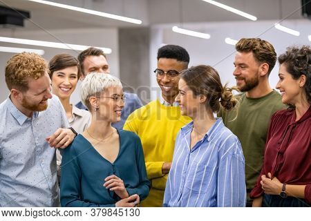 Successful creative group of casual business people talking to each other in modern office. Happy multiethnic businessmen and businesswomen standing as a team and laughing together in co-working space