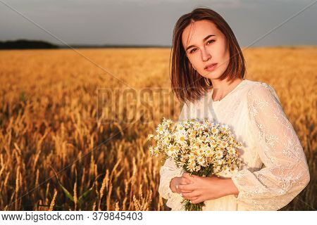 Beautiful Woman In A White Dress With A Bouquet Of Flowers In A Wheat Field At Sunset. Free Lifestyl