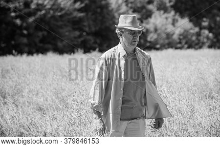 Mature Man At Field, Lifestyle Older Men. Older Senior Man Wear Blue Skirt And Hat, Casual Style At