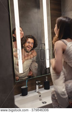 Beautiful Young Couple In Love Wearing Pajamas Standing In Front Of Bathroom Mirror Next To A Sink,