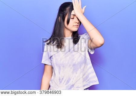 Young beautiful girl wearing casual t shirt surprised with hand on head for mistake, remember error. forgot, bad memory concept.
