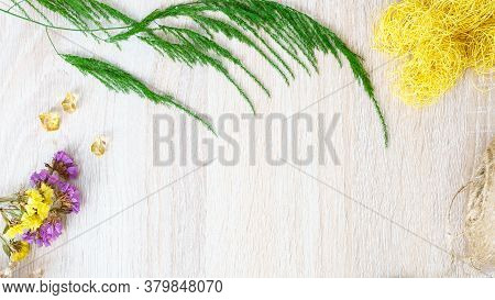 Asparagus, Yellow Sisal And Yellow And Lilac Flowers On A Wooden Background. Free Ad Space.