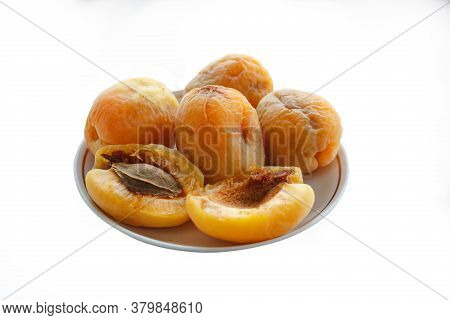 Group Of Old Apricots With Apricot Pits In A Ceramic Plate Isolated On A White Background.