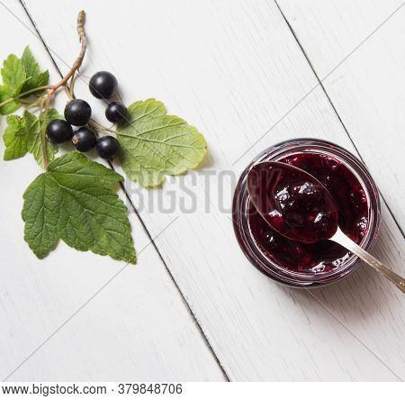 Currant Homemade Jam In Glass Jar On The White Wooden Table Decorated With Black Currant And Green L