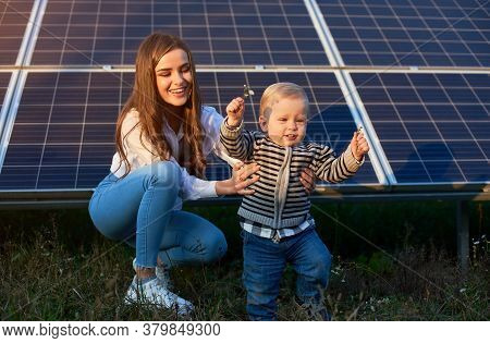 Young Mother Supporting Her Little Son In Making His First Steps Near Solar Panels, Concept Of Moder