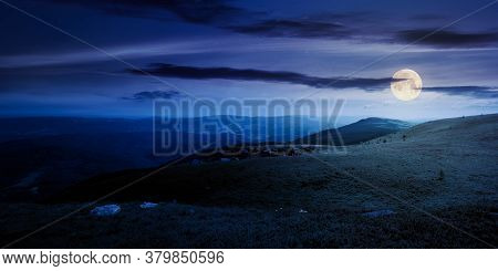 Meadow With Rocks On Grassy Alpine Meadow At Night. Mountain Scenery In Summer Full Moon Light. Clou