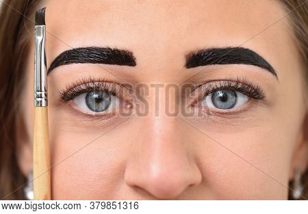 Young Woman Dyed Her Eyebrows With Henna And Holds A Brush Next To Her Face