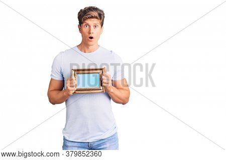 Young handsome man holding empty frame scared and amazed with open mouth for surprise, disbelief face