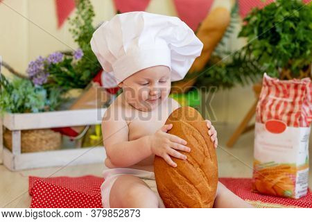 A Baby In A Cook's Hat Sits Back In A Beautiful Photo Zone With Flour And Vegetables, A Cook's Child