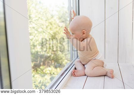 Baby Boy 8 Months Old Sitting In Diapers On The Window Sill And Looking Into The Distance, A Place F