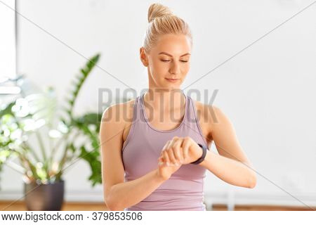 technology and healthy lifestyle concept - young woman with fitness tracker at home or yoga studio