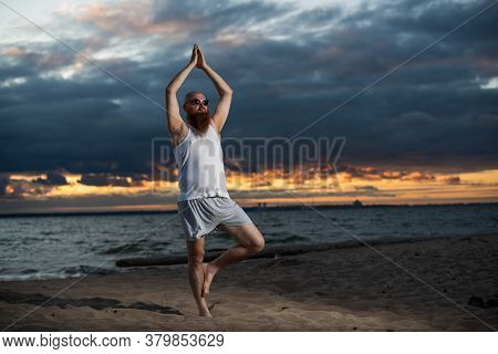A Bald Man With A Red Beard Practices Yoga On The Beach At Sunset. A Funny Dude In A T-shirt And Sun