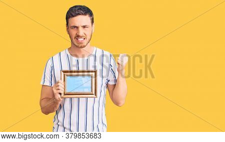 Handsome young man with bear holding empty frame annoyed and frustrated shouting with anger, yelling crazy with anger and hand raised