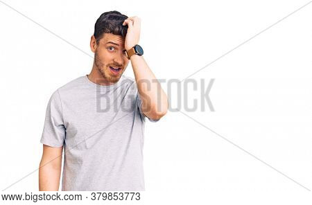 Handsome young man with bear wearing casual tshirt surprised with hand on head for mistake, remember error. forgot, bad memory concept.