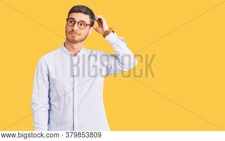 Handsome young man with bear wearing elegant business shirt and glasses confuse and wondering about question. uncertain with doubt, thinking with hand on head. pensive concept.